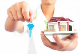 Man holding house key and house model