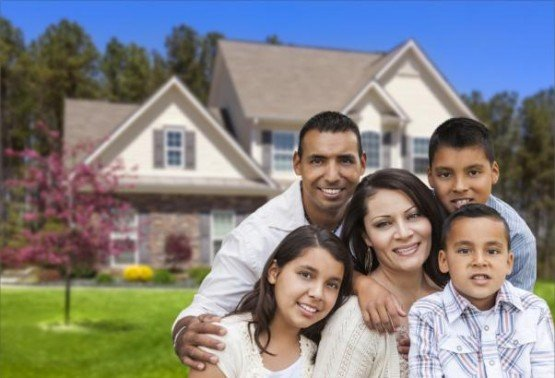 Happy Hispanic Family Portrait in Front of Beautiful House.