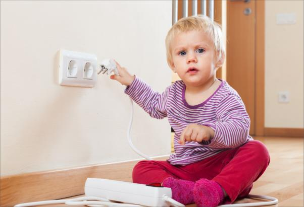 Baby playing with electrical extension and outlet on floor