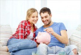 smiling couple with piggybank sitting on sofa