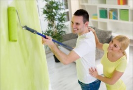 Smiling young couple painting their hew home