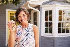 woman-with-keys-standing-outside-new-home-P6WPYU4