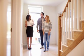 realtor-showing-young-couple-around-property-for-PRUUFP3