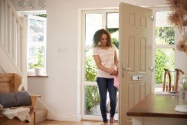 woman-returning-home-and-opening-front-door-P2ZEYTY